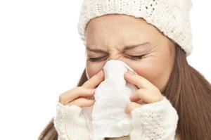 Girl in winter clothing sneezing