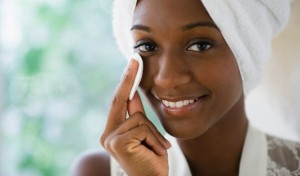 Black woman wiping face with cotton pad